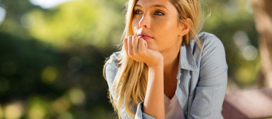 41330505 - thoughtful woman sitting alone outdoors